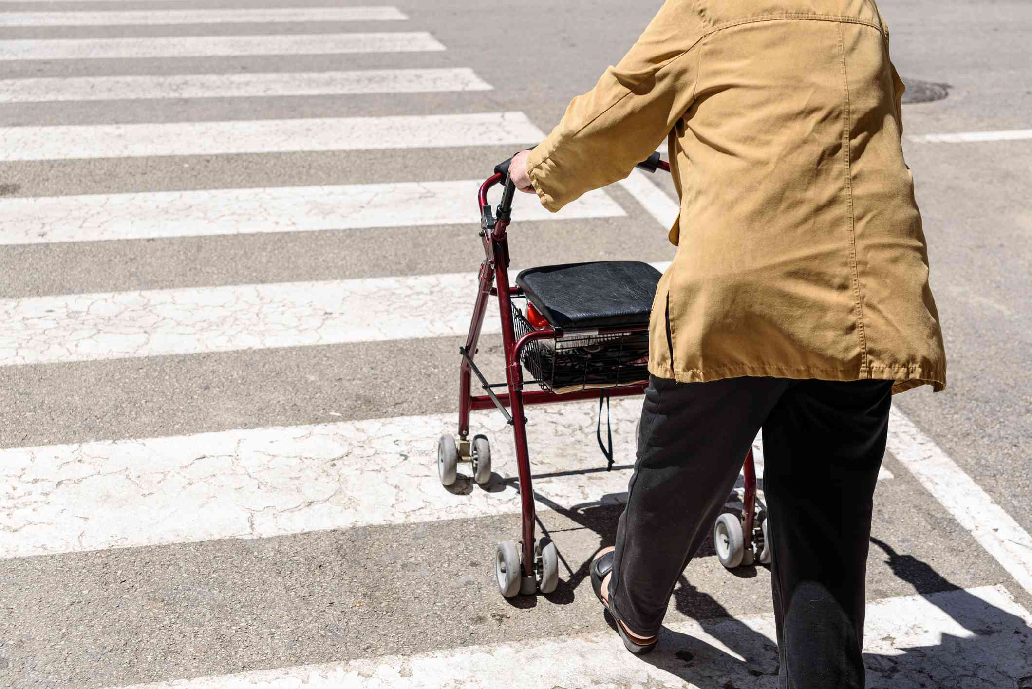 An old person crossing the road using a walker.