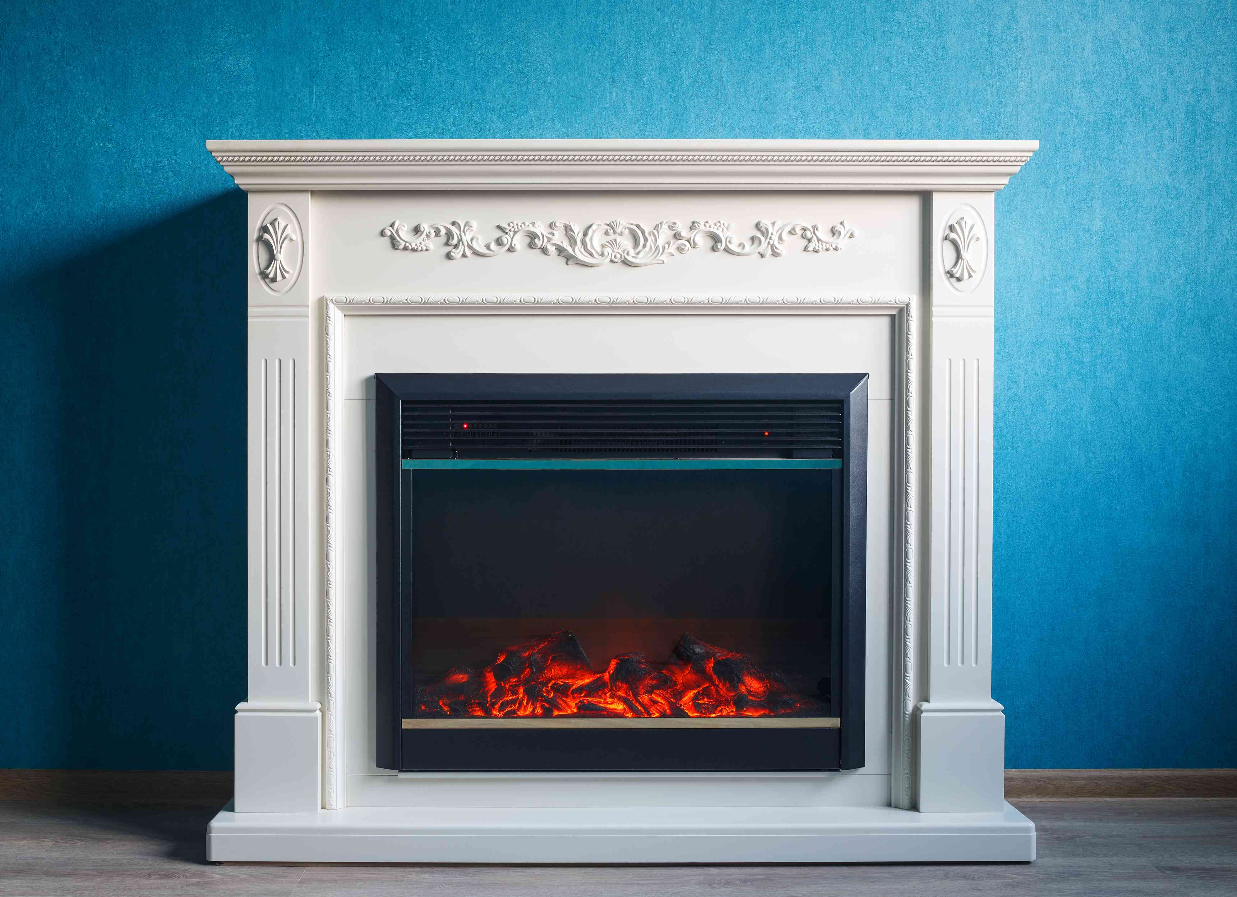 Electric fireplace with white exterior detailing against a blue wall