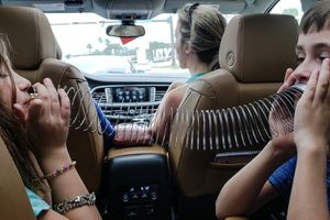 kids playing with slinky in back of car