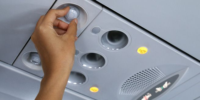 A hand adjusts the air vent over an airplane seat