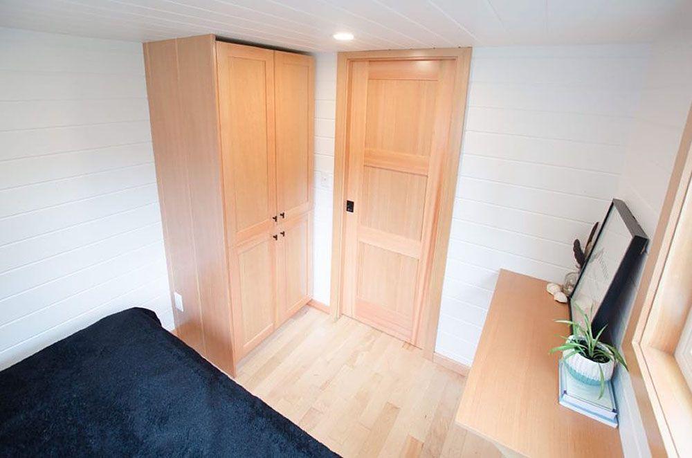 A wooden cabinet next to a bedroom door