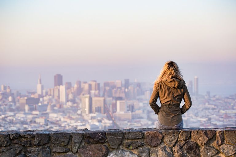 Person sitting on a stone wall overlooking a large cityscape