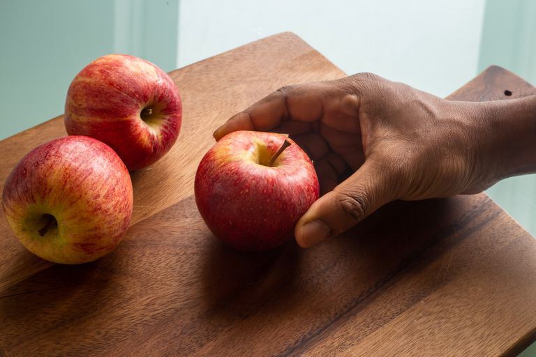 man's hand holding an apple on a cutting board next to to other apples