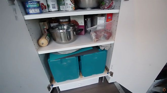 View of pots and boxes inside kitchen cabinet