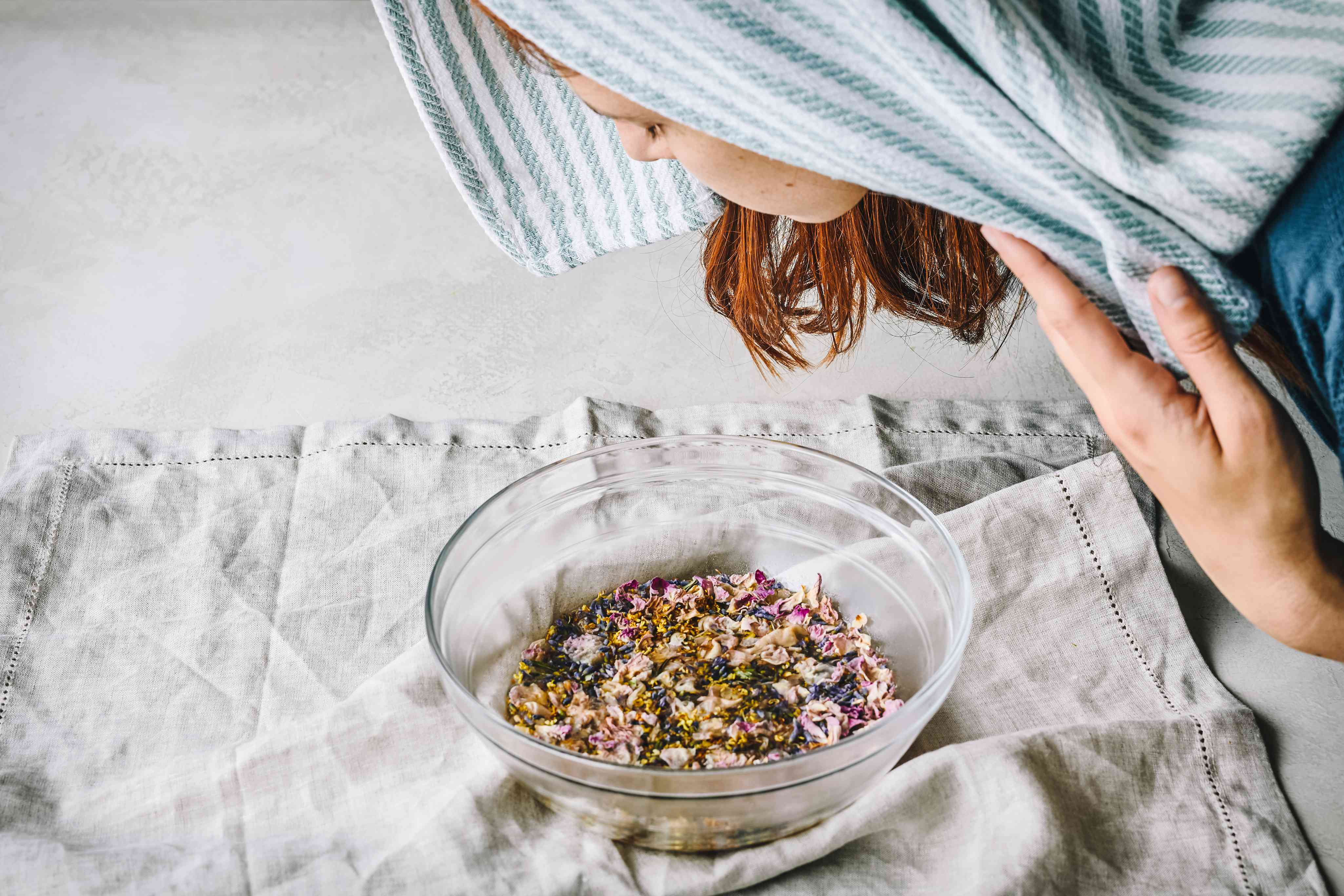 side profile of woman immerses her face in hot steam facial from glass bowl with flowers