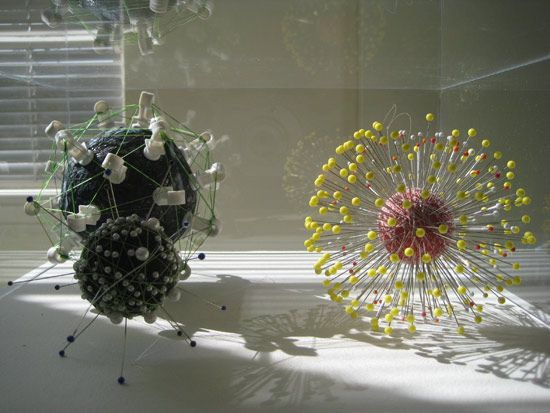 Orbs made out of garbage under glass.