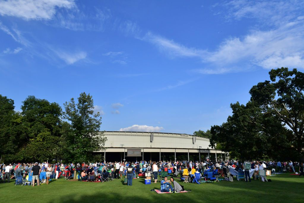 Crowd gathered on the green lawn in front of Tanglewood, a cream-colored curved building surrounded by tall green trees with a blue sky and a few white clouds above