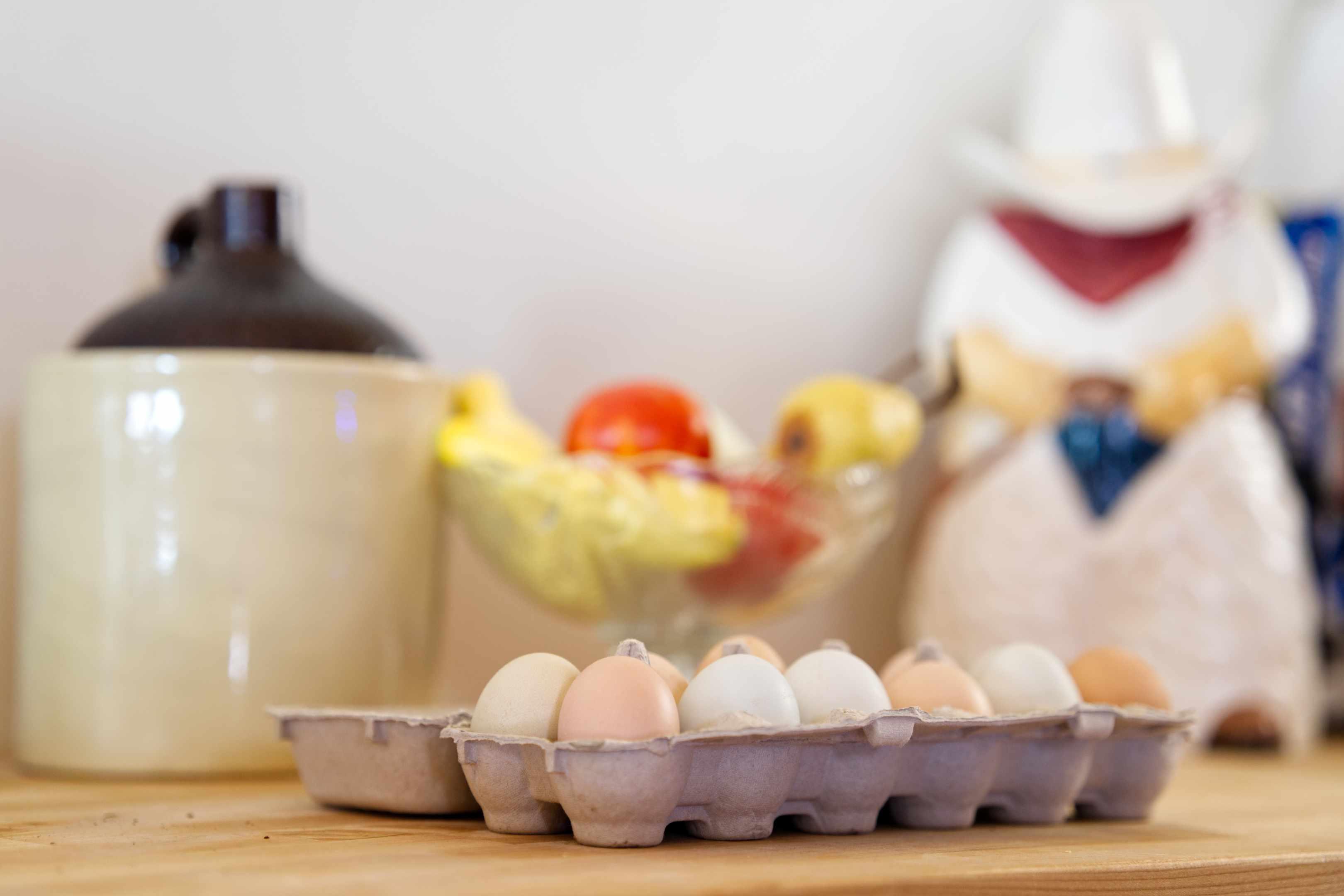 farm fresh eggs in carton sit on kitchen counter next to cookie jar