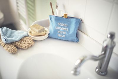 A blue cosmetics bag on a sink with natural soap and a loofah.
