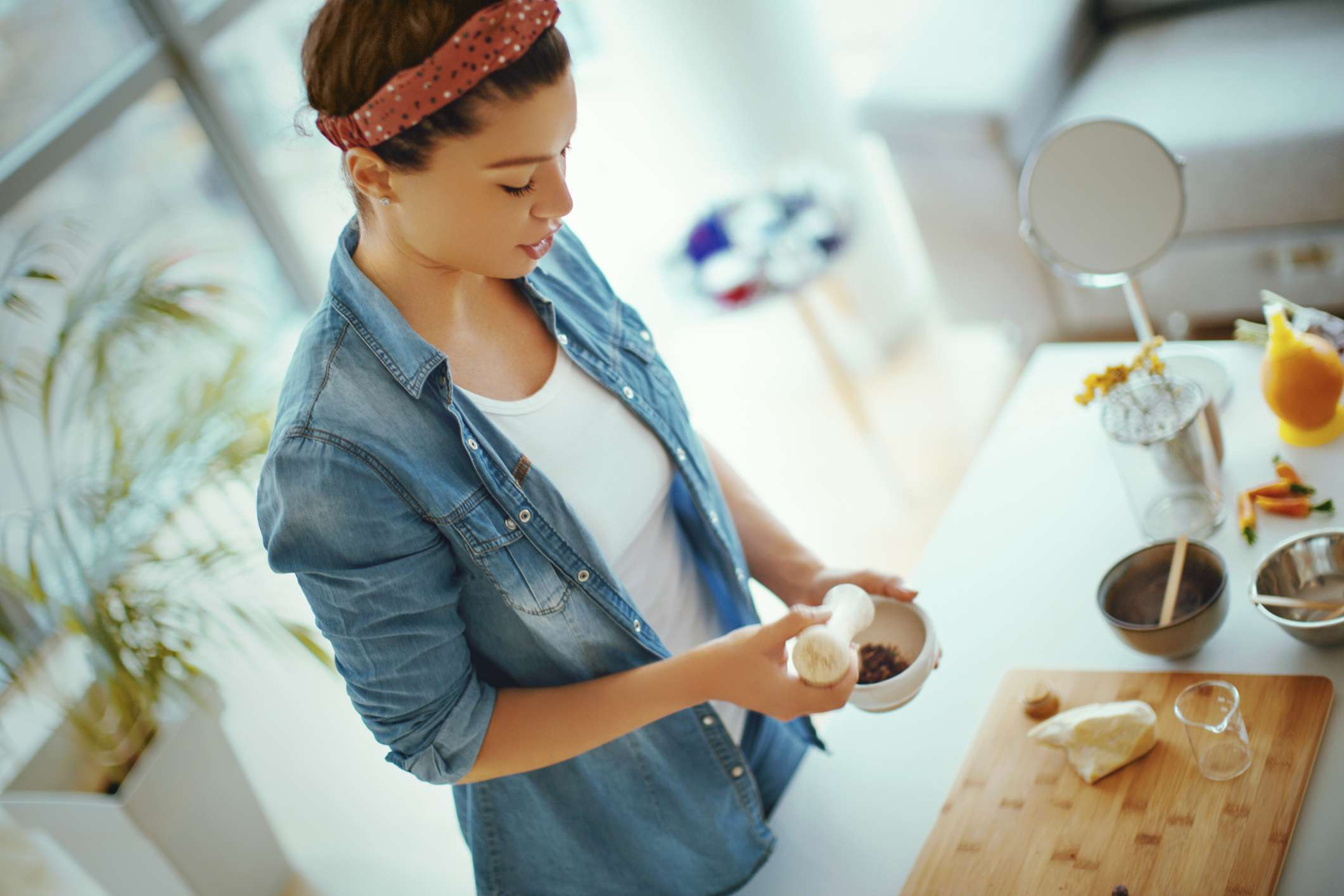 A young white woman making her own cosmetics at home.