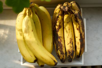 two banana bunches side by side in dappled sun, one fresh, one bruised and brown