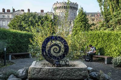 A spiral sculpture in a garden of trees and hedges with stone buildings in the background