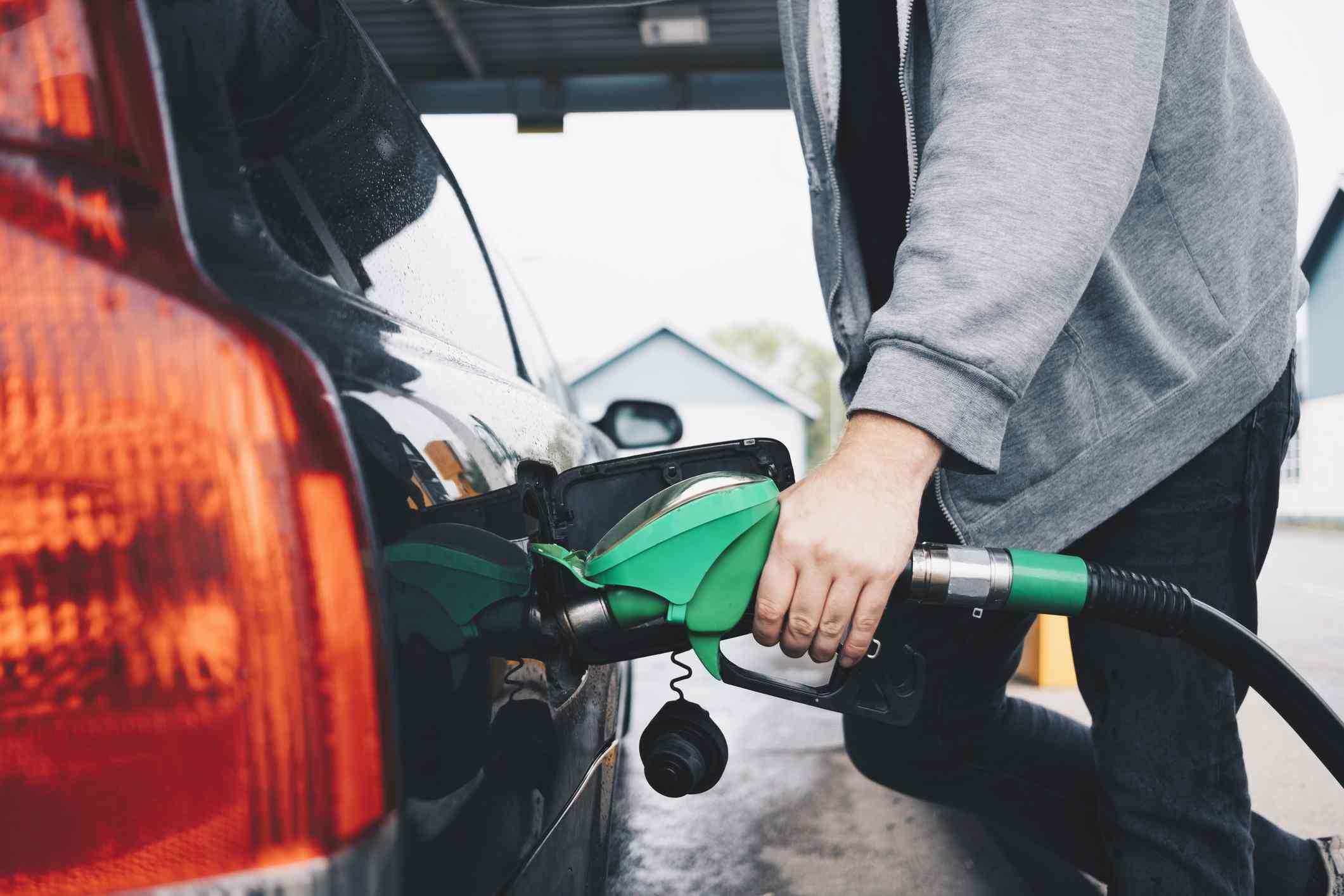 A man putting gas into the tank of his car.
