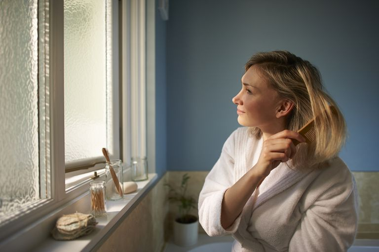 A blonde woman brushes her hair looking out the window of her blue bathroom.