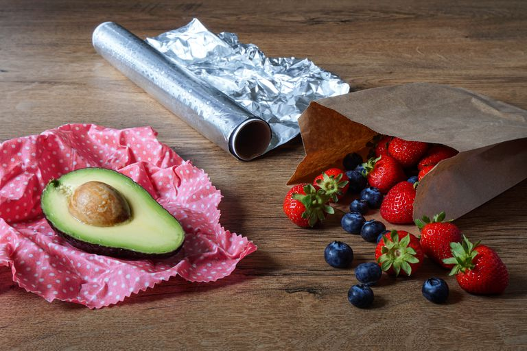 composition of aluminium foil, cut avocado in beeswax wrap, and berries spilled out of brown paper bag