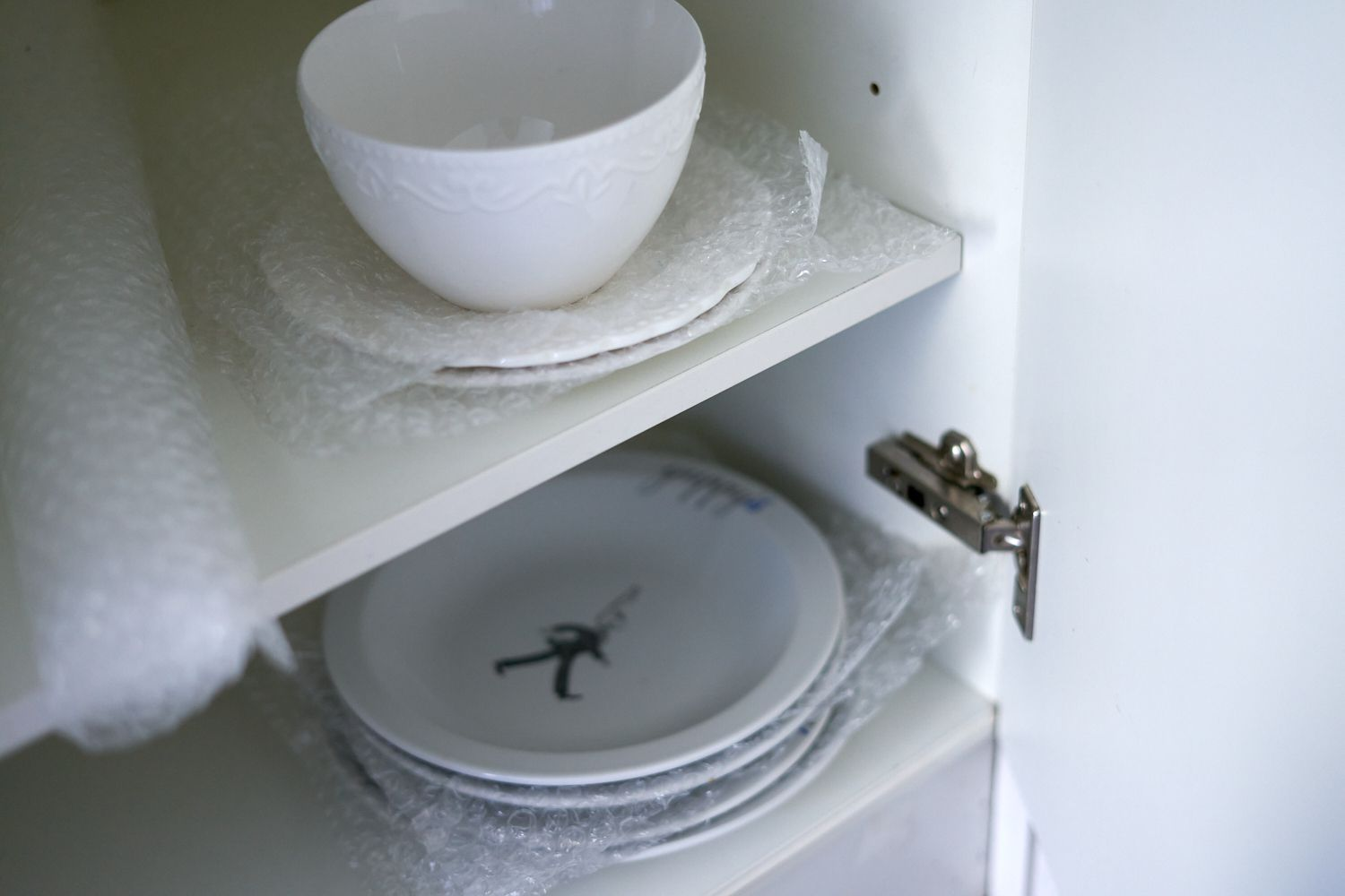 plates and bowls in kitchen cabinet wrapped in bubble wrap