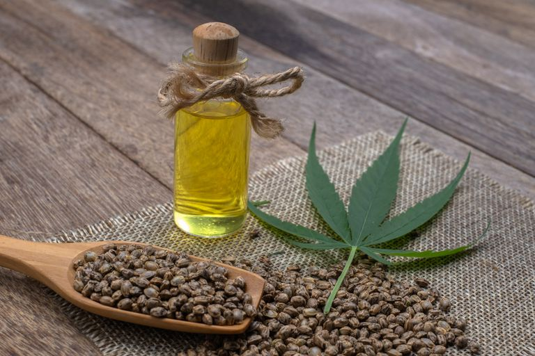 Hemp oil in a glass bottle tied with a bow Hemp seeds in a wooden spoon on the table. The concept of bringing hemp oil Extracted as a medicine By natural methods. Doctors and marijuana.