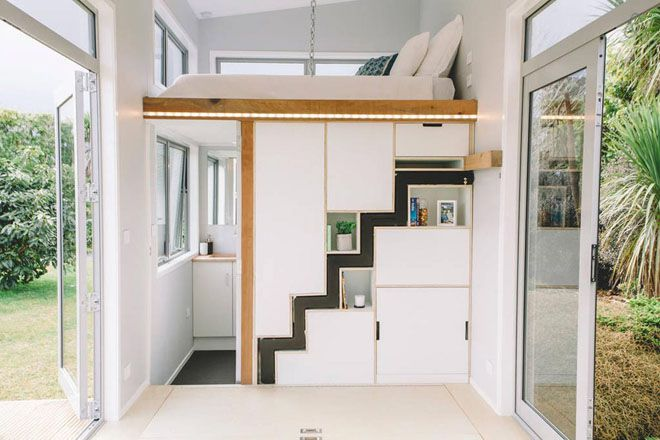 Storage wall and sleeping loft with a hidden staircase