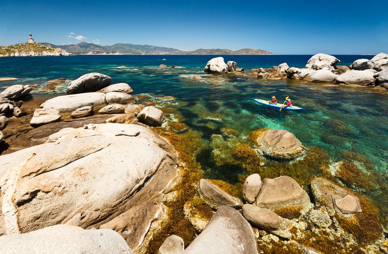 pair of kayakers in the crystal clear waters surrounded by rocks off the southern coast of Sardinia