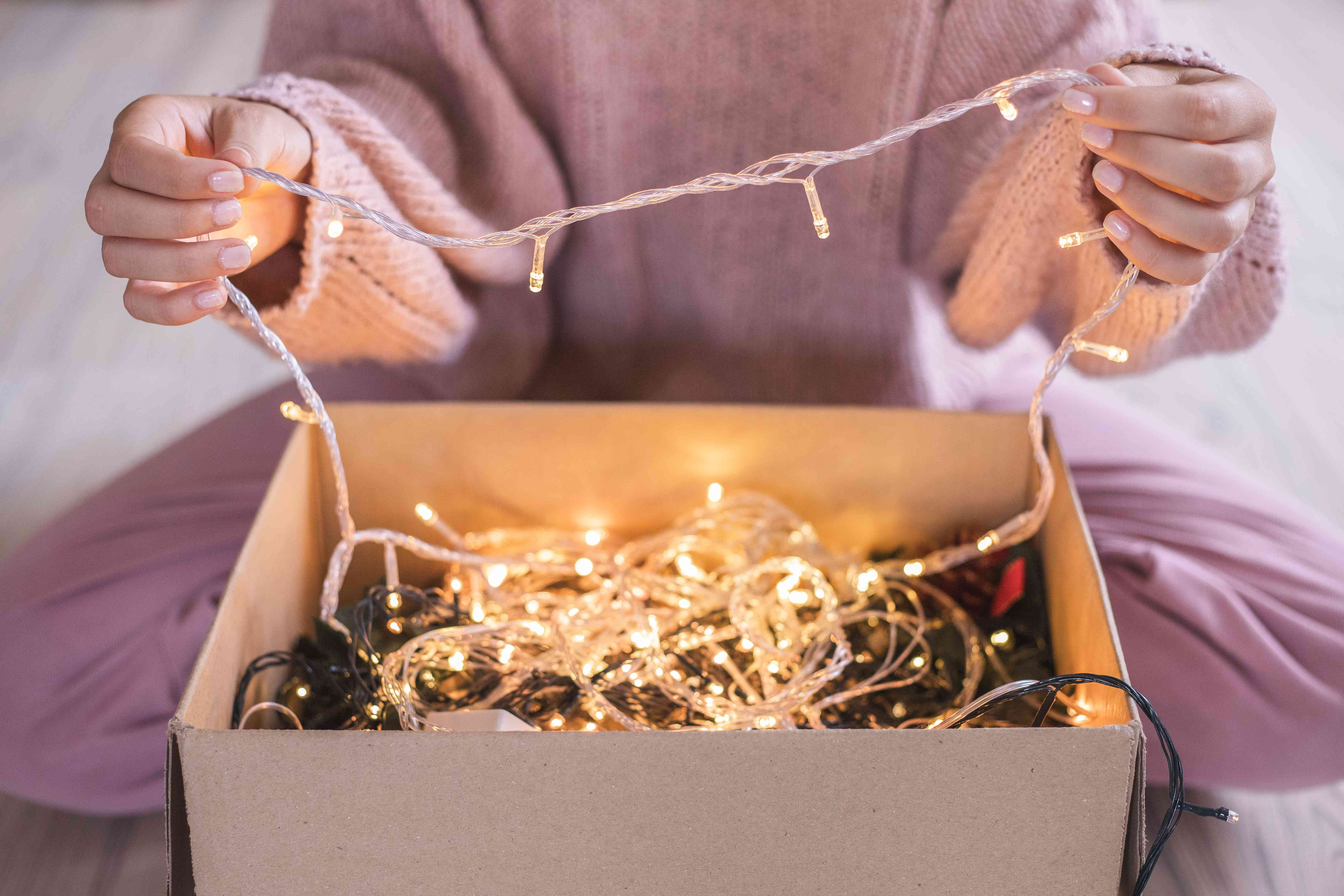 woman in pink sweater and pants pulls out strand of glowing Christmas lights from box