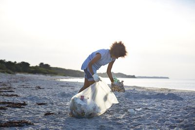 Person collecting trash from beach and putting it in bag