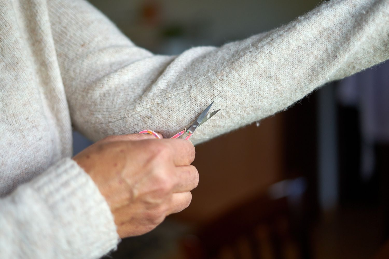 person wearing cream sweater carefully cuts pills off outstretched arm with small scisscors