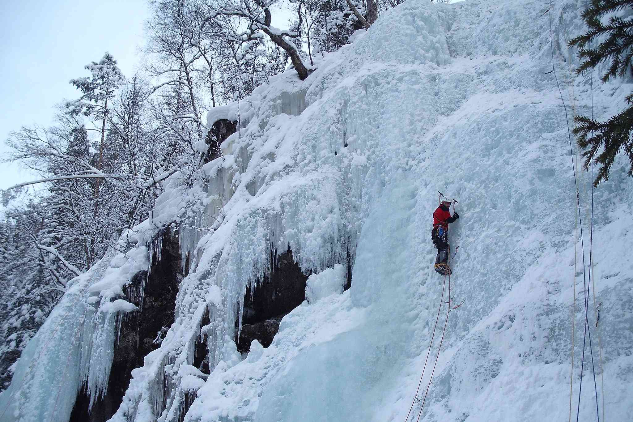 Climber ascends a frozen ravine in Rjukan, Norway