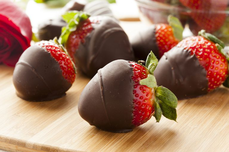 Chocolate covered strawberries on a wooden counter