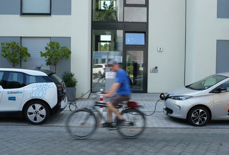 cyclist passing charging electric cars