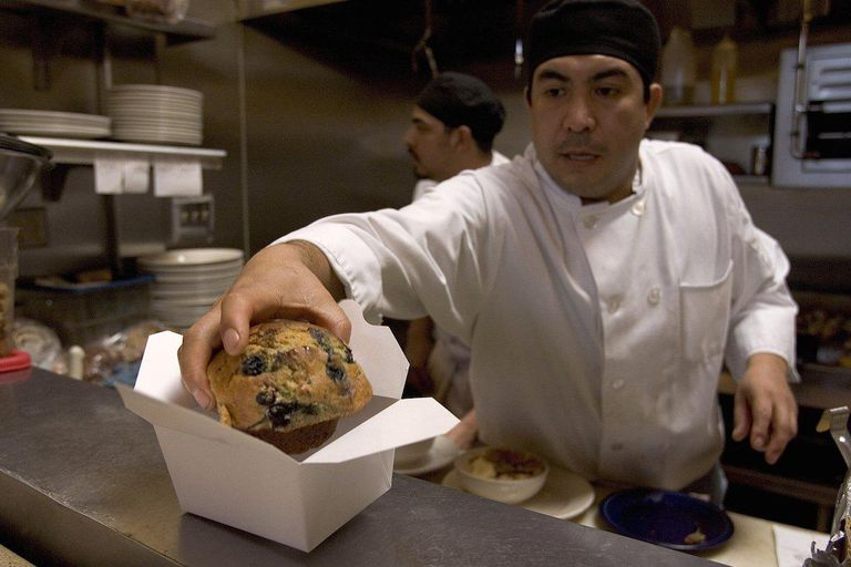 chef placing muffin in takeout container