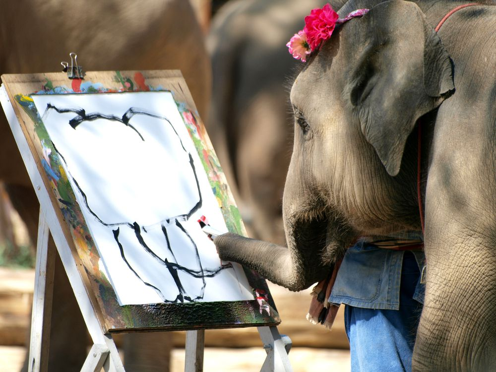 an elephant holding a paintbrush with its nose, painting a picture of an elephant