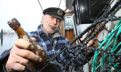 Fisherman pulling an old bottle from fishing net