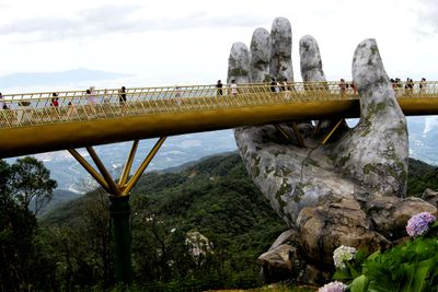 The golden Cau Vang bridge appears to be held by a large stone hand near Danang, Vietnam