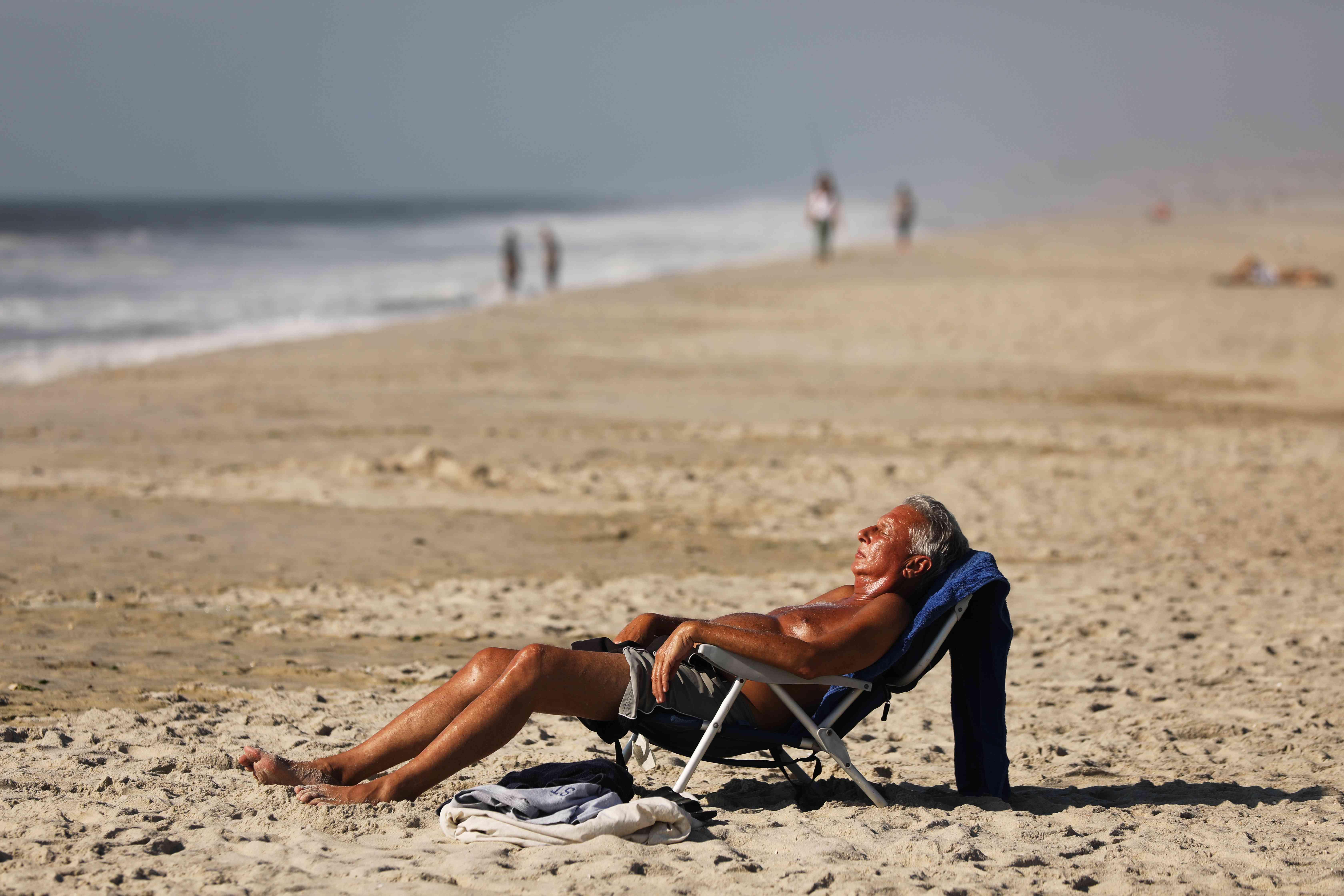 A man sunning on the beach.