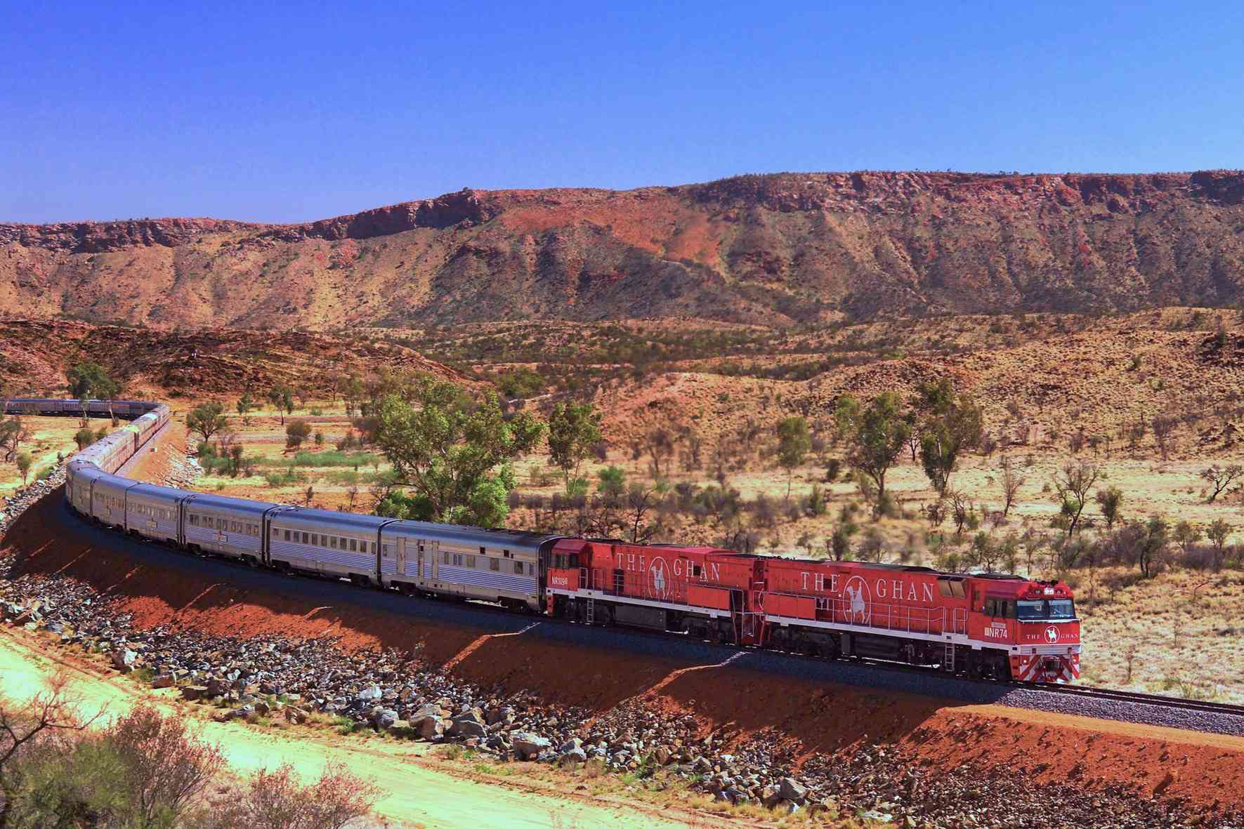 The Ghan snaking through Australian Outback with mountains in background