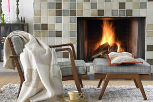 Armchair and footrest in front of tiled fireplace. Pillow and blanket and a cup of tea. Big soft rug on the floor.
