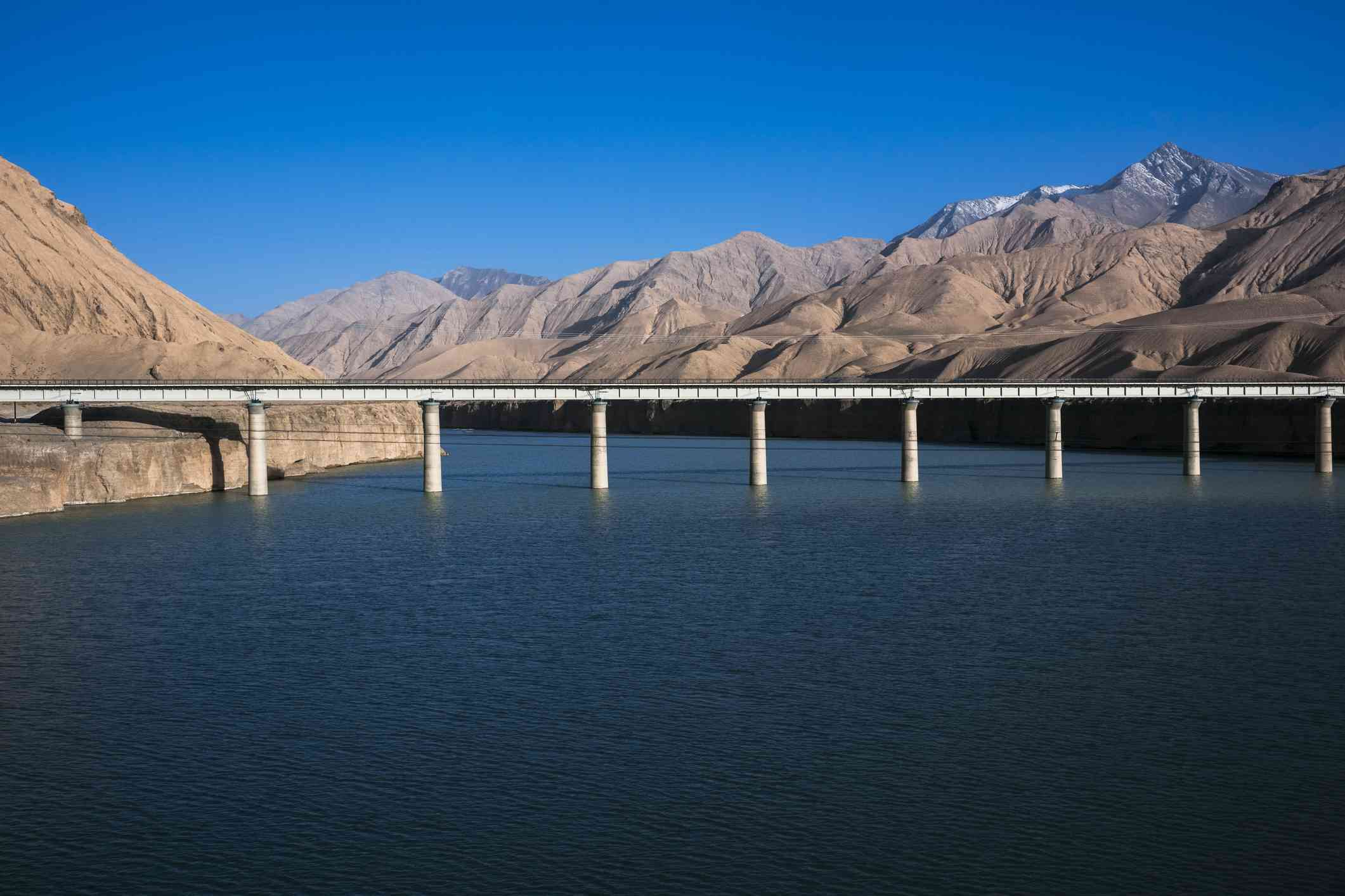 Qinghai-Tibet Railway tracks crossing over water, surrounded by mountains