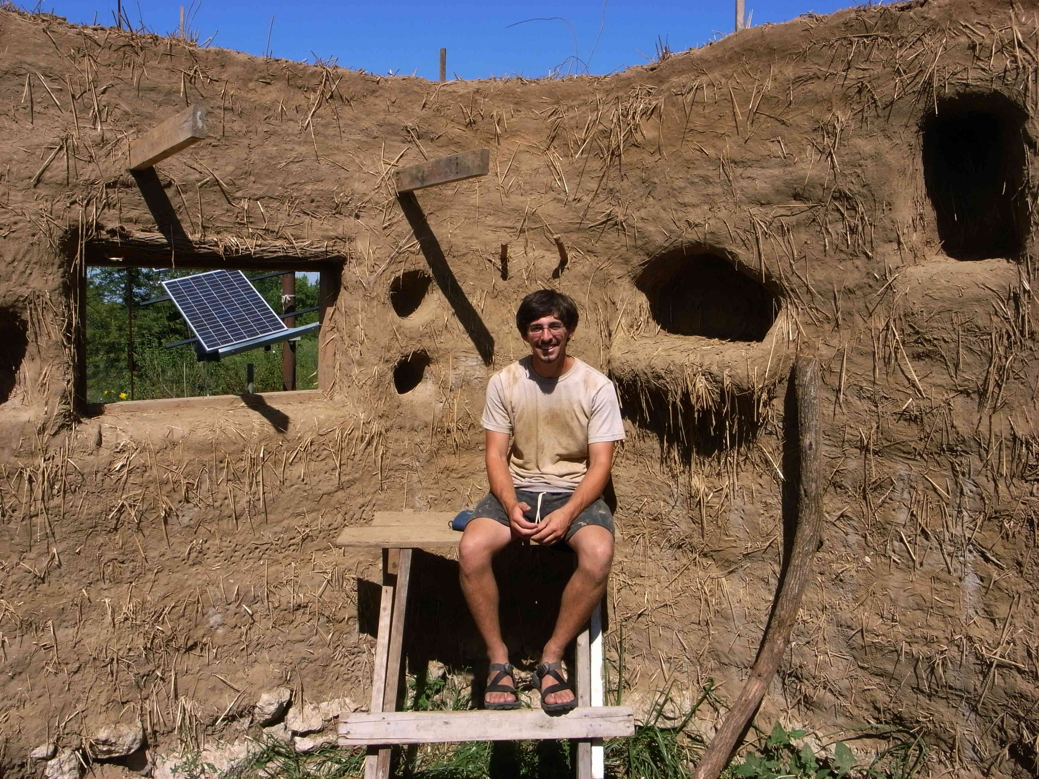 Builder Ziggy sits in his cob house that he built by hand.