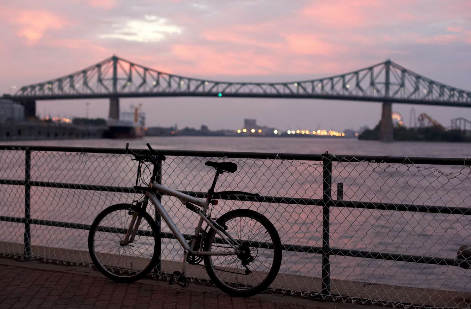 A bike leans against a railing in front of the Jacques Cartier Bridge in Montréal at sunset