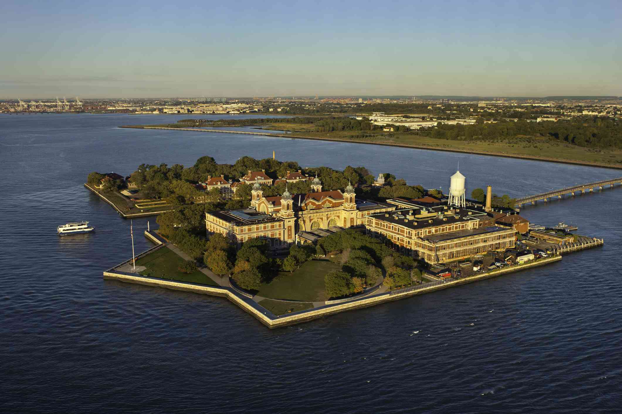 aerial view of the historic buildings and green space of Ellis Island, an island surrounded by the Hudson River in Manhattan, New York