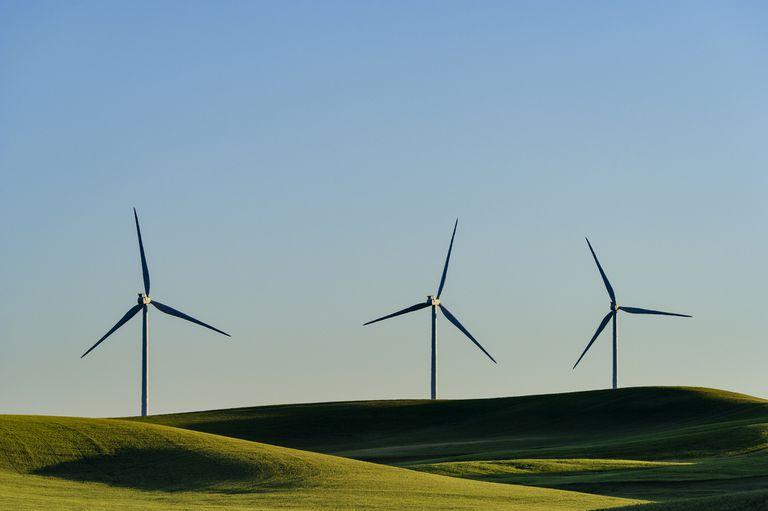 Three wind turbines on a landscape of rolling hills and blue sky.