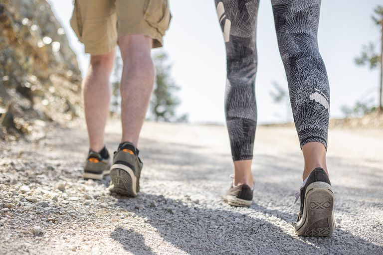 guy in shorts woman in leggings walk up white gravel trail