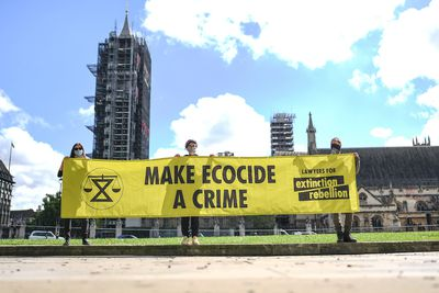 People holding a banner reading 'Make Ecocide a Crime' in Parliament Square on August 28, 2020 in London, England.