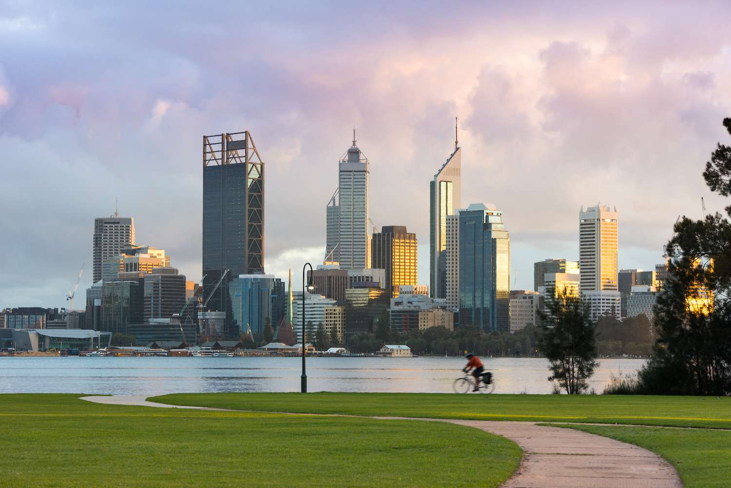 A cyclist pedals in front of the Perth skyline on a cloudy morning