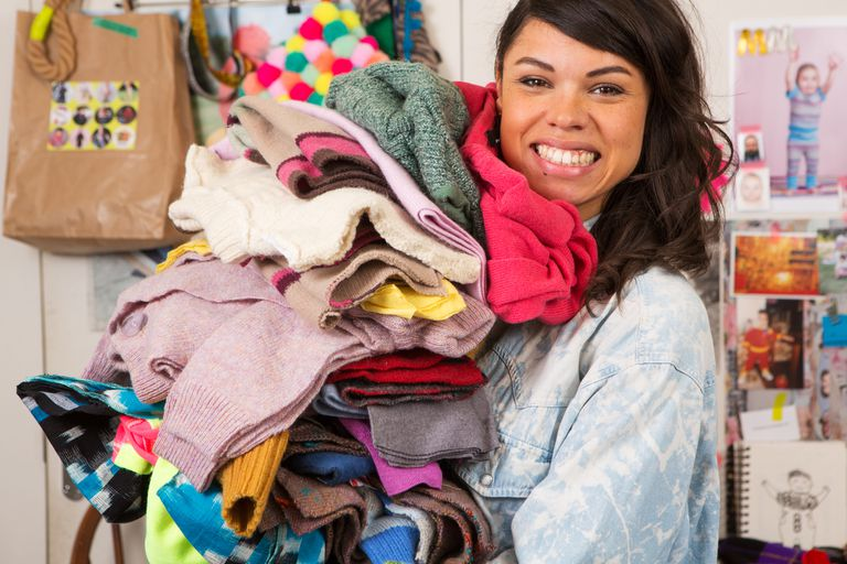 smiling woman holding a pile of sweaters