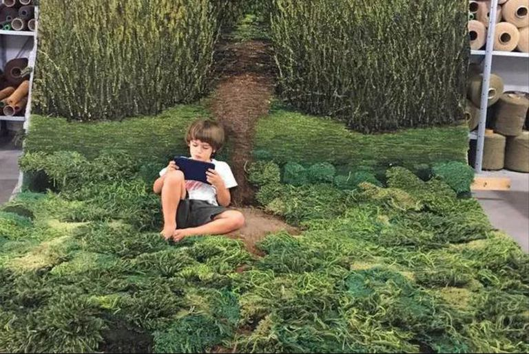 Child reading a book inside on a rug that looks like meadow