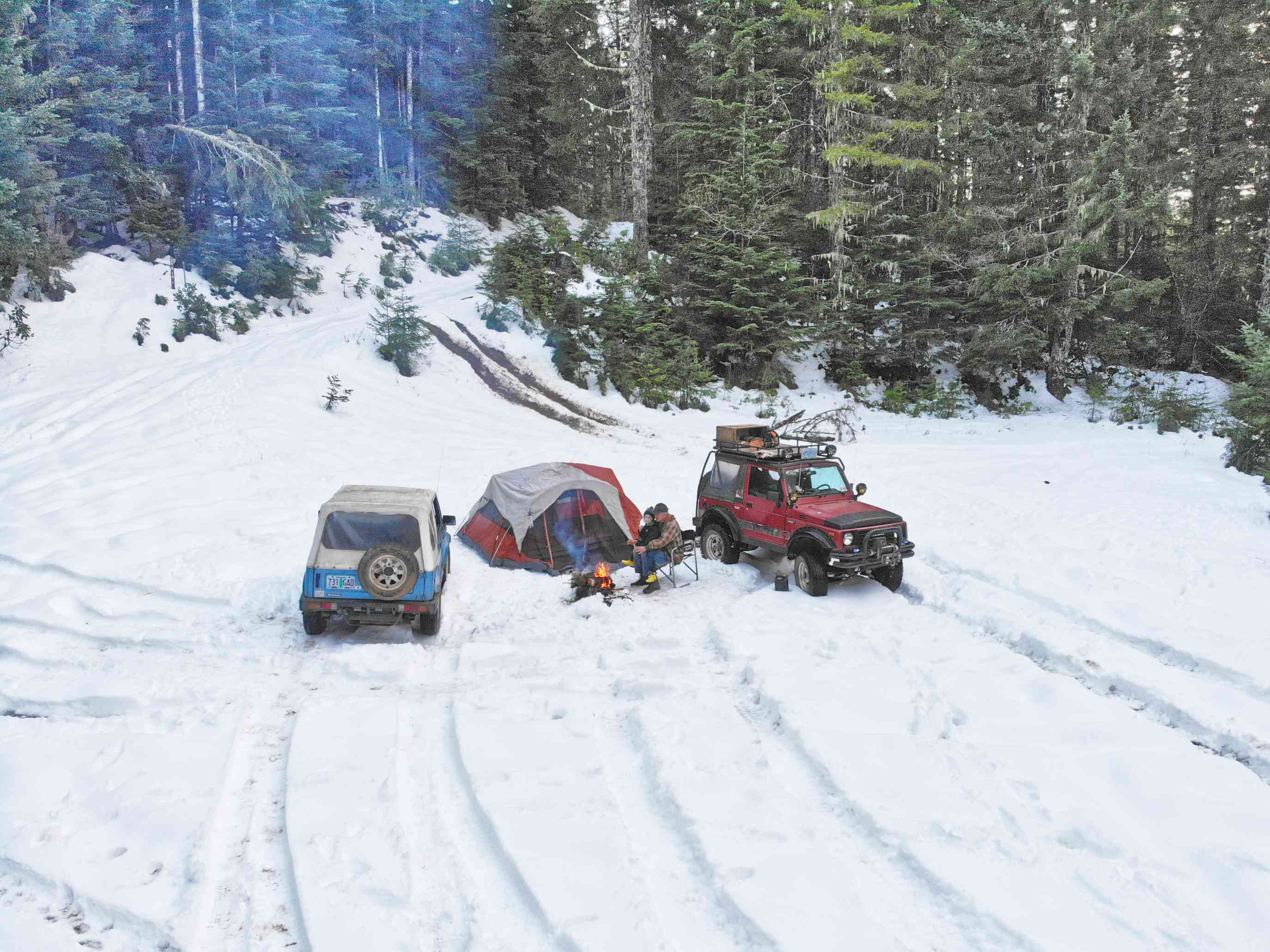 two jeeps in deep snowy forest with campsite